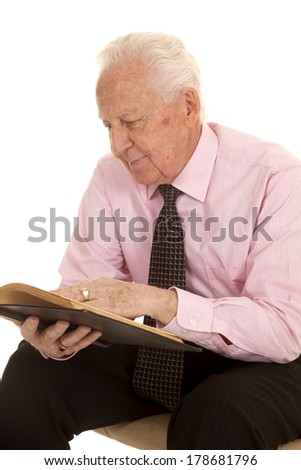 An elderly man reading and studying a book. - stock photo