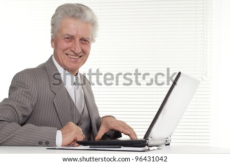 an elderly man sitting at the laptop on a background
