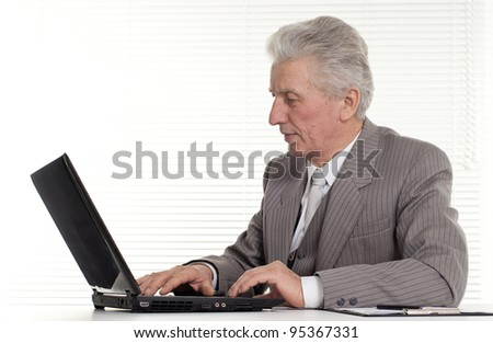 an elderly man sitting at the laptop on a isolate
