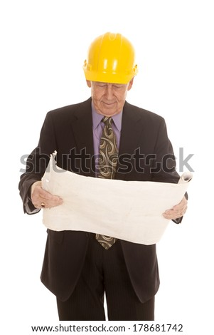 an elderly man wearing his hardhat and looking down at his plans. - stock photo