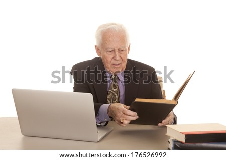 An elderly man with a laptop and some books in a suit and tie.