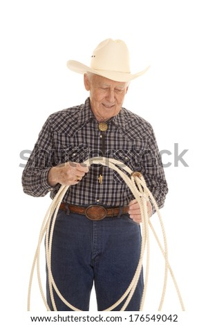 An elderly man with a rope and a cowboy hat. - stock photo