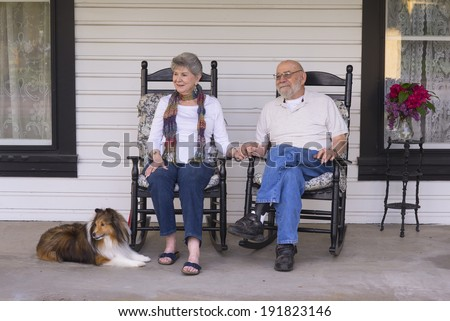 An elderly married couple in their eighties watch the world go by from their porch with their sheltie dog by their side. - stock photo