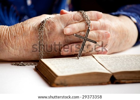 An elderly pair of hands holding a cross - stock photo
