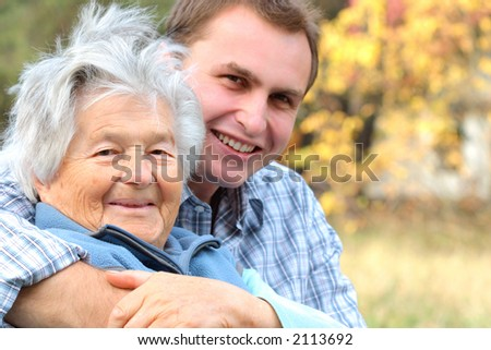An elderly person hugged by her grandson.Focus on woman.