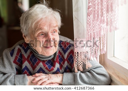 An elderly woman, a grandmother, with a smile looking out the window sitting in the kitchen. - stock photo
