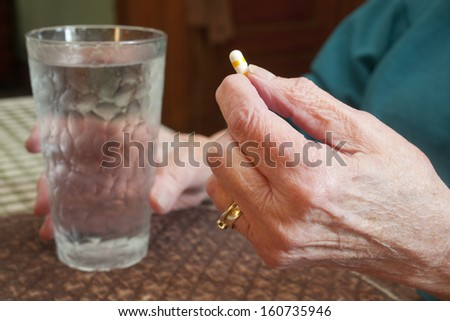 An elderly woman about to take a pill. - stock photo