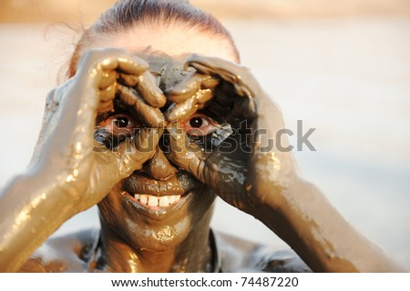 An elderly woman enjoying the natural mineral mud on face sourced from the dead sea in background - stock photo