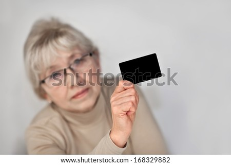 An elderly woman holding a plastic card