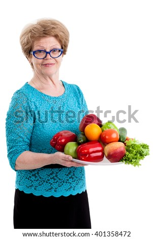 An elderly woman holding a tray with fruits and vegetables in hands, isolated white background - stock photo