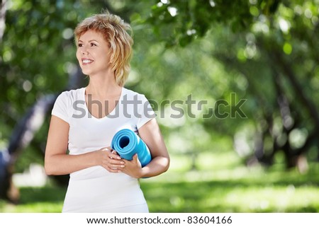 An elderly woman in a park with a gymnastic mat - stock photo