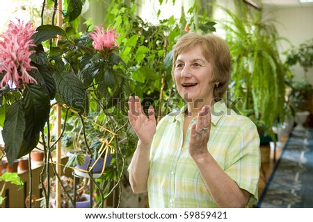 An elderly woman  in a winter garden looks at a flower with a delight