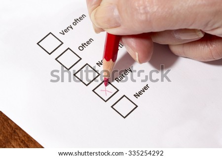 An elderly woman is filling a survey form with a red pencil. The person is answering rarely to the questionnaire. The focus point is on the red pen tip.