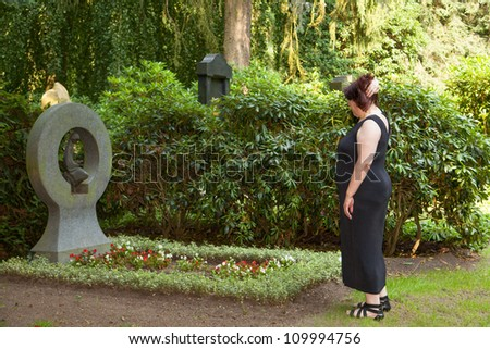 An elderly woman mourns at the cemetery about her dead husband deceased husband - stock photo