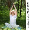 An elderly woman practices yoga in nature. The symbol of healthy lifestyle - stock photo