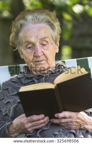 An elderly woman reading a book sitting in a hammock. - stock photo