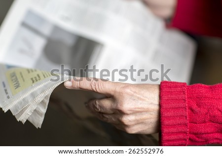An elderly woman reading a newspaper. - stock photo