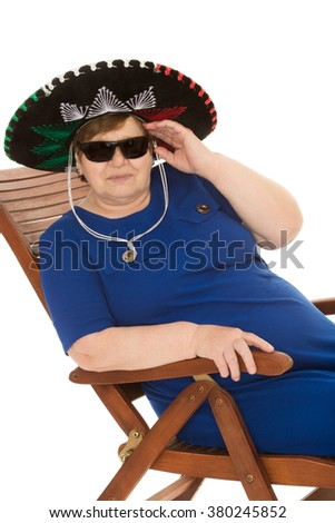 An elderly woman rests on a chair. In my grandmother's Mexican sombrero. Grandmother looking at the camera through black sunglasses - Isolated on white background - stock photo