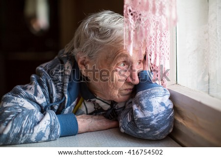 An elderly woman sadly looking out the window. - stock photo