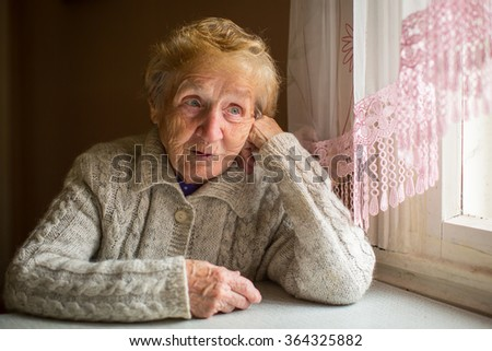 An elderly woman sits in the house near the window. - stock photo