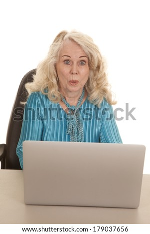 an elderly woman sitting at her desk by her computer with a shocked expression on her face.