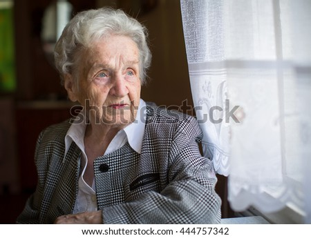 An elderly woman, sitting at the table, a portrait. - stock photo