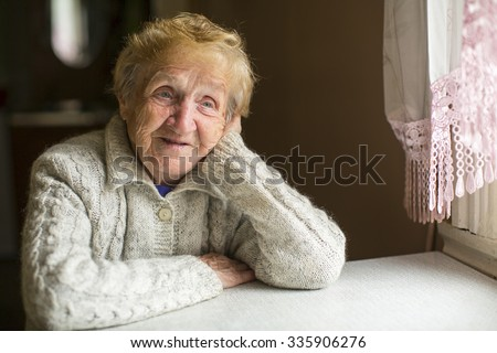 An elderly woman sitting dreamily by the window. - stock photo