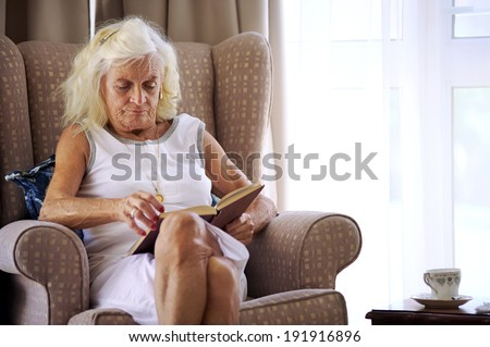 An elderly woman sitting on her couch reading a book - stock photo