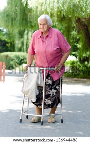 An elderly woman standing with her walker in nature