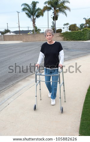 An elderly woman uses a walker to assist her balance while walking on the sidewalk. - stock photo