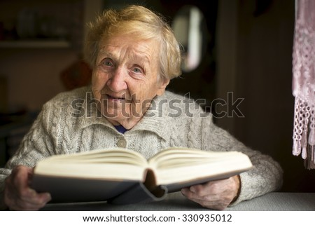 An elderly woman with a book sitting at the table. - stock photo