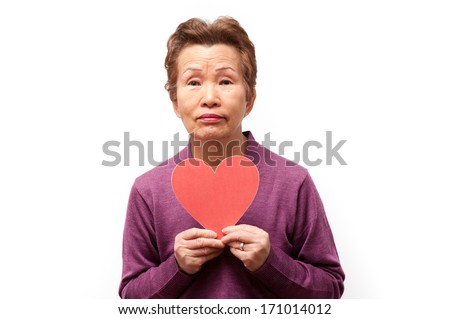 An elderly woman with a red heart