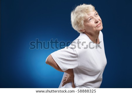 An elderly woman with a sick back on a blue background - stock photo