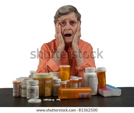 An elderly woman with a table full of medications looking overwhelmed and confused - stock photo