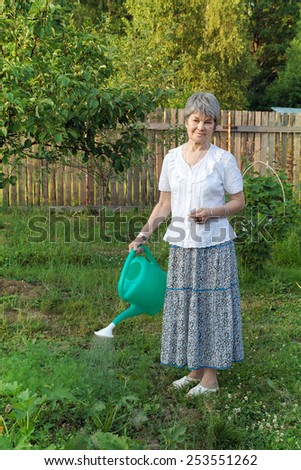 an elderly woman with a watering can in the garden - stock photo