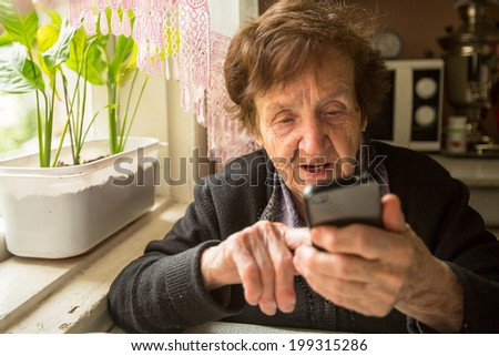 An elderly woman with smartphone. - stock photo