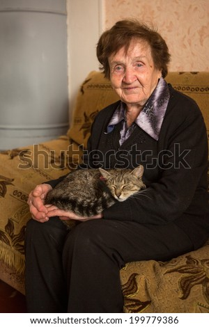 An elderly woman (80 years) with cat in her house. - stock photo