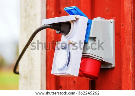 An electric socket timer with cord attached. This one is used outdoors in damp weather which might present a safety issue. Water drops on casing. - stock photo