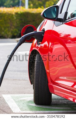 An electric vehichle, car charging at a public station - stock photo
