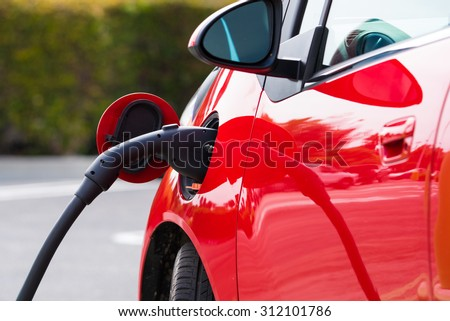 An electric vehicle, car charging at a public station - stock photo