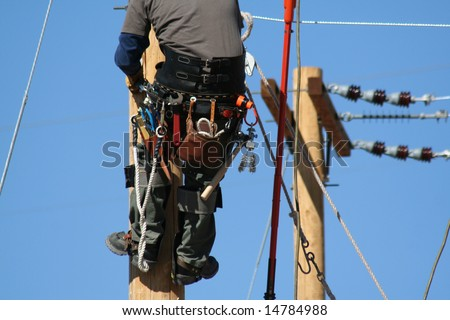 an electrical lineman apprentice working on a pole at a lineman college - stock photo