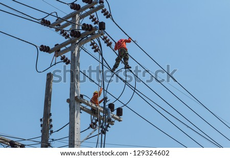 An electrical power utility worker fixes the power line. - stock photo