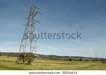 An electrical pylon in a field with a blue sky