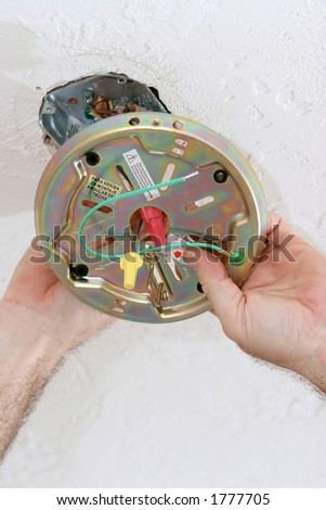 An electrician attaching a ceiling fan plate to a ceiling box.  All work is being performed by a licensed master electrician according to National Electric Code standards. - stock photo