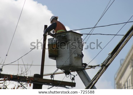 An electrician, high on a lift, works the wires.