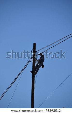 An electrician silhouetted against the blue sky at the top of a pole while performing maintenance on electric powerlines - stock photo