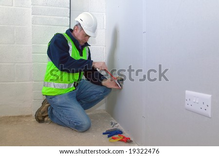 An electrician wearing safety gear installing an electrical socket - stock photo