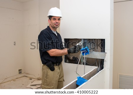 An electrician working on a home remodel wearing safety gear.