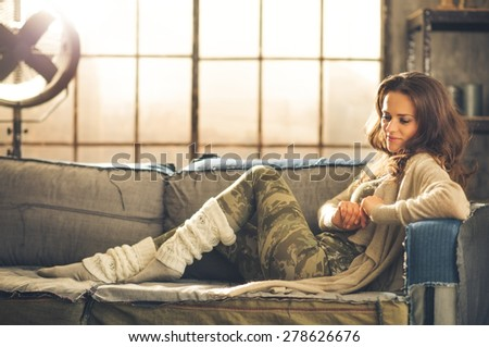 An elegant brunette woman smiling and looking down is wearing comfortable, casual clothing, leggings, and a cardigan and is relaxing on a loft sofa. Industrial chic ambiance and cozy atmosphere. - stock photo