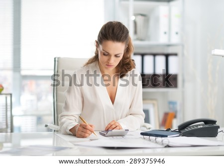 An elegant businesswoman is concentrating while sitting at her desk in a modern office, crunching numbers. - stock photo